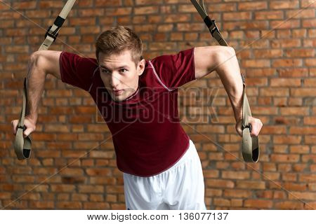 Fit young sportsman is doing push-ups in gym. He is standing and looking forward with aspiration. Man is leaning hands on trx straps