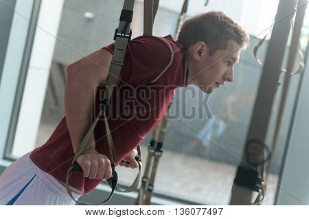 Muscular male athlete training his body in gym. He is standing and doing push-ups with trx straps