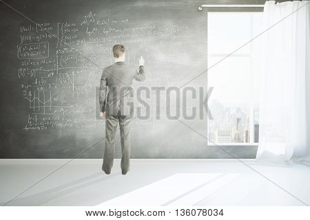 Businessman writing mathematical formulas on chalkboard wall in room with concrete floor window with curtain and city view. 3D Rendering