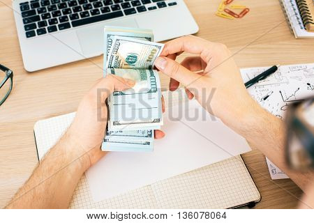 Top view of man counting money above wooden office desktop with various items. Bribery and corruption concept