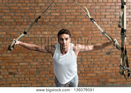 Confident young sportsman is training his body with trx equipment. He is stretching his arms sideways and looking forward with aspiration