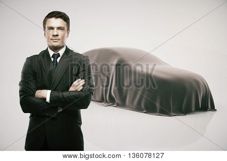 Businessman with crossed arms standing in front of car covered with grey veil on light background. Car developer presenting new product