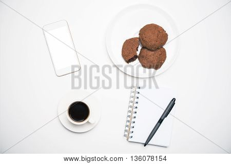 Top view of office desktop with blank white cellular phone notepad and pen coffee cup and cookies on plate. Mock up