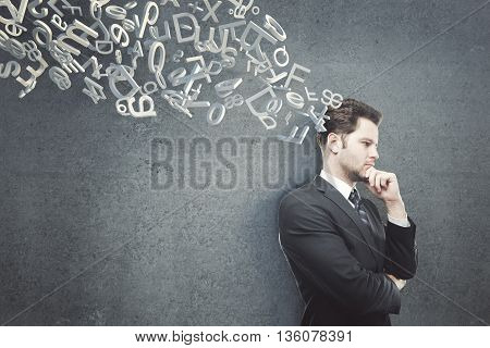 Thinking businessman with hand at chin standing against dark concrete wall