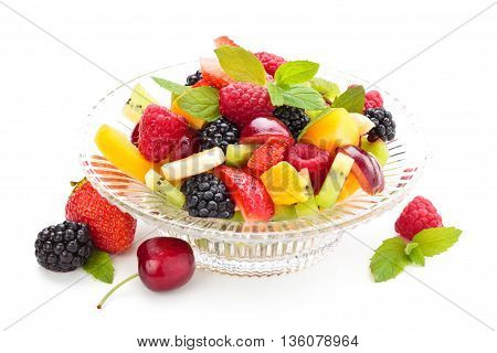 Fruit salad with mint leaves in a glass bowl.