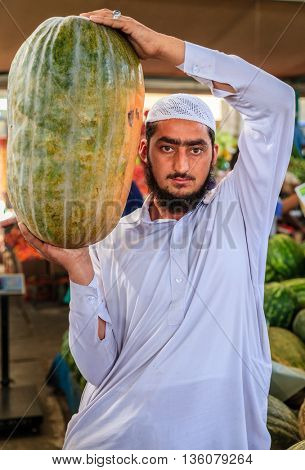 Dubai, June 4, 2016: a local vendor with a giant squash at the fruit and vegetable market in Dubai, UAE