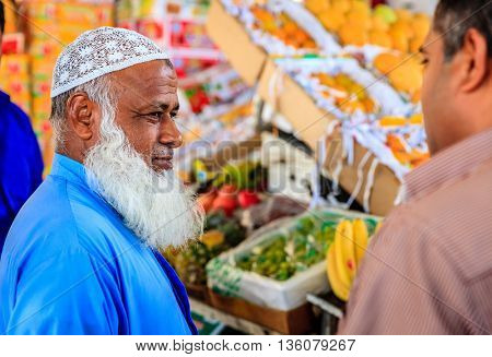 Dubai, June 4, 2016: a farmer negotiating with a customer at the fruit and vegetable market in Dubai, UAE