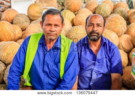 Dubai, June 4, 2016: farmers in front of pile of squashes at the fruit and vegetable market in Dubai, UAE