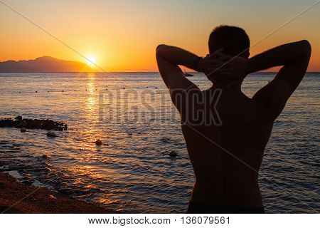 Young man standing with hands behind his head enjoying beautiful colorful sunrise or sunset sea landscape and fresh air
