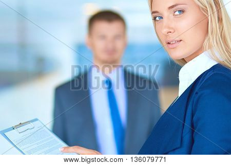 Businesswoman standing in office holding documents in hand .