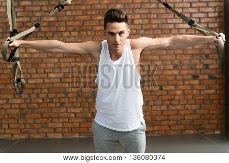 Attractive fit sportsman is training his body with trx equipment. He is standing and stretching arms sideways. Man is looking at camera with confidence