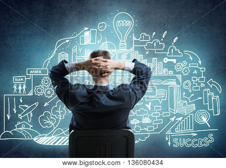 Rear view of businessman sitting in office chair and looking at sketched business plan
