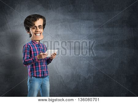 Funny bigheaded student with tablet on chalkboard background