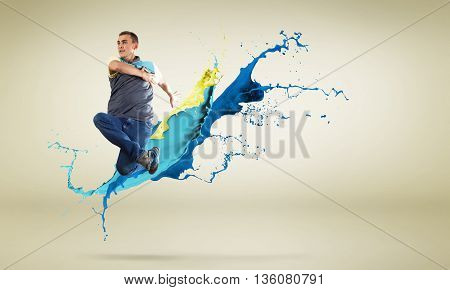 Modern style dancer in jump and color paint splashes at background