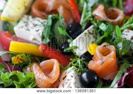 Salmon salad with brie and olives closeup. Smoked salmon, brie, olives, lettuce and pepper mix with herbs. Mediterranean tasty snack background