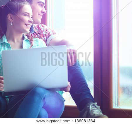 Portrait of young couple moving in new home sitting with laptop..