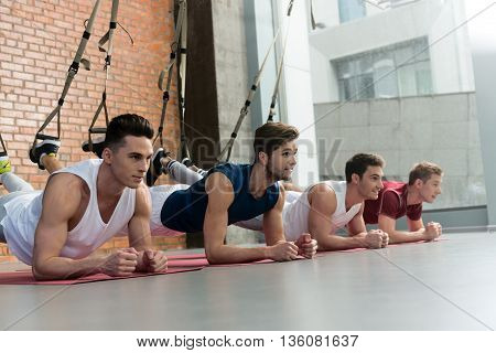 Cheerful four sportsmen training in gym. They are leaning legs on trx equipment and smiling