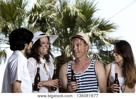 young people talking and laughing with a bottle of beer in their hands palms and blue sky in the background