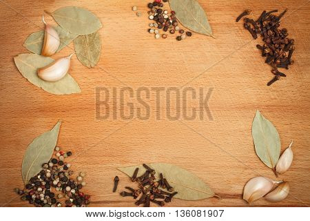 Wooden background framed with different spices with empty space in central part