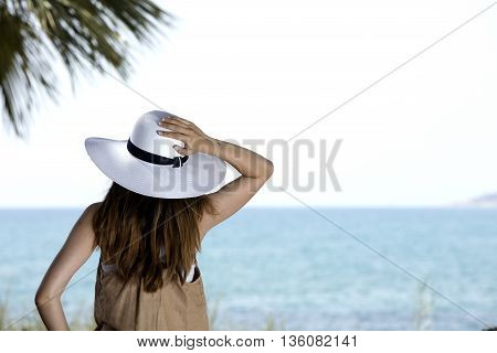 young girl looking the horizon with a white straw hat