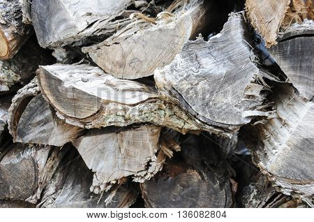A pile of old weathered split fire wood.