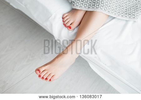 Beautiful female legs not covered top view void. Woman sticked her legs out of gray blanket. Naked legs with red pedicure on end of bed. Some free space