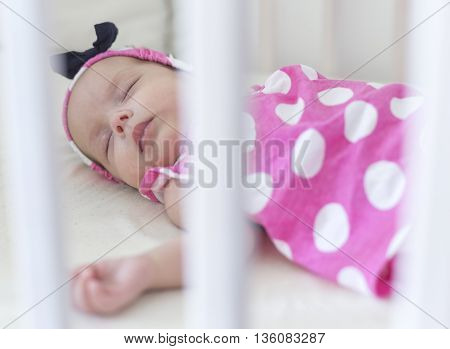 beautiful newborn baby sleeping in a crib in dotted dress