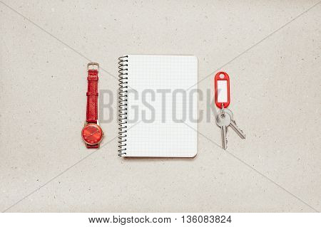 Empty notepad with keys and red wrist watch on paper background, red trinket