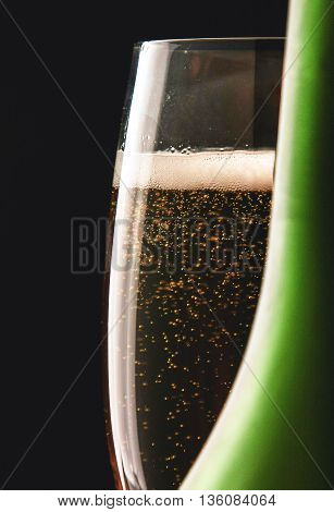 A glass of sparkling champagne on black background.