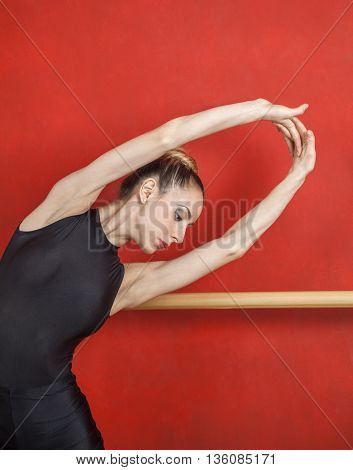 Ballerina Stretching With Hands Raised Against Red Wall