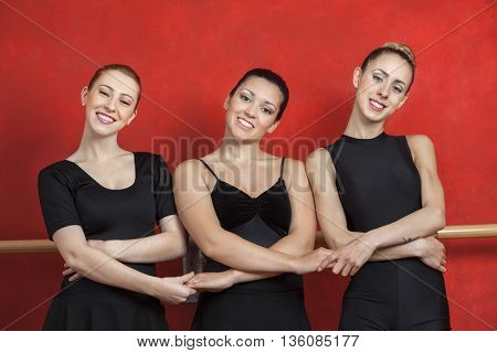 Portrait Of Ballerinas Holding Hands In Studio