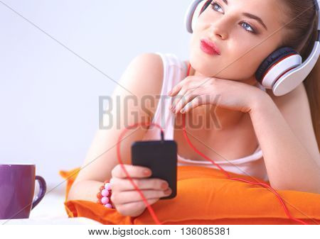 Young woman lying on floor and listen to music.
