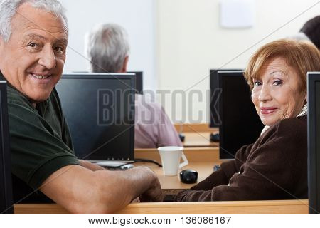Confident Senior Man And Woman Sitting In Computer Class