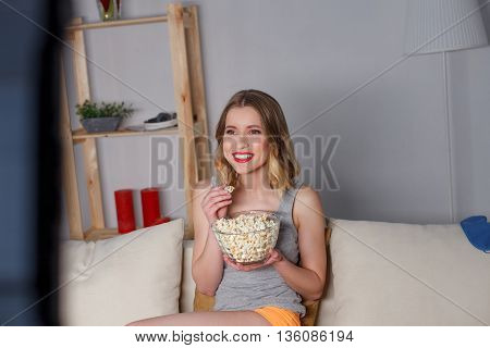 Happy young woman is watching television and smiling. She is sitting on couch. Girl is holding a bowl and eating popcorn
