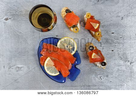 Tasty various italian sandwiches with seafood against rustic wooden background. Crostini with cheese red fish and olives on white plate glass of wine horizontal top view