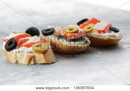 Tasty various italian sandwiches with seafood against rustic wooden background. Crostini with cheese crab sticksand sliced olives horizontal view close up with selective focus