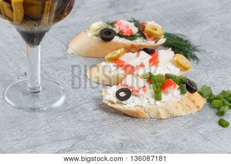 Tasty various italian sandwiches with seafood against rustic wooden background. Crostini with cheese crab sticks and olives herbs and wine close up horizontal view with selective focus
