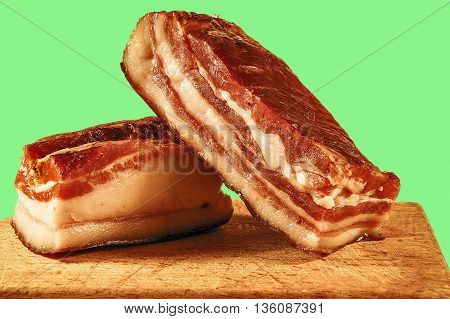 Two pieces of meaty smoked bacon home on a kitchen cutting board.