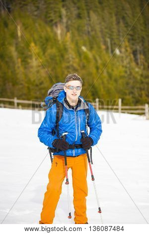 Mountain Climber Walks On A Snowy Slope.