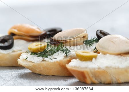 Tasty various italian sandwiches with seafood against rustic wooden background. Crostini with cheese mussels and sliced olives horizontal view close up with selective focus