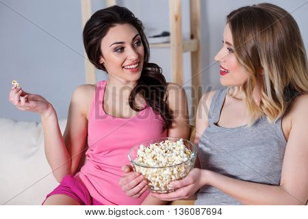 Best friends are talking and smiling. They are sitting on sofa and smiling. Girls are eating popcorn while watching movie