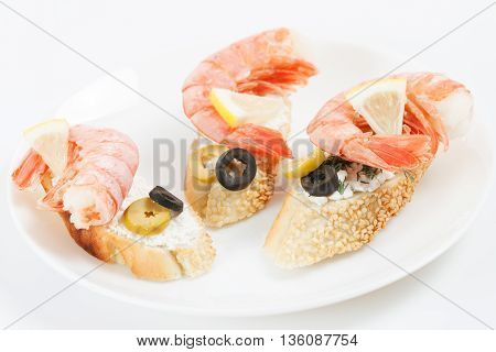 Tasty various italian sandwiches with seafood against white background. Crostini with cheese giant shrimps lemon sliced olives on white plate close up with selective focus