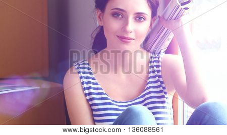 Girl sitting on windowsill at new home.