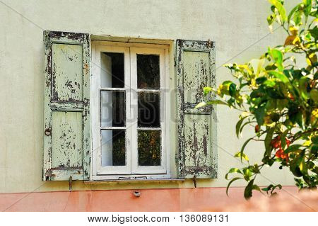 Old  scratched white window with light green shutters
