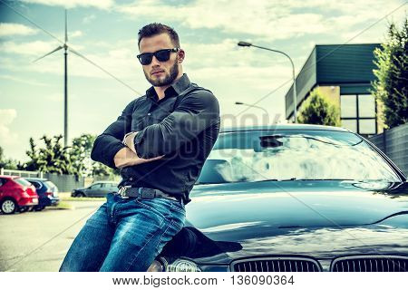 Portrait of brutal young bearded man in sunglasses with crossed arms leaning on his new polished car outdoor