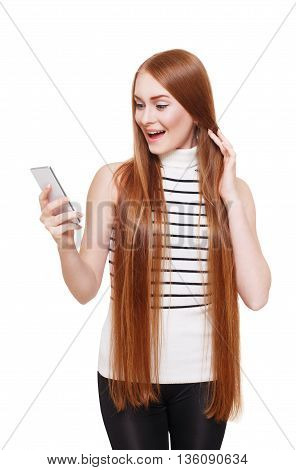 Portrait of happy smiling woman looking at mobile excited. Young redhead long-haired girl get message on cell phone. Female portrait isolated at white, modern communication technology concept.