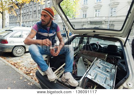 ZAGREB, CROATIA - OCTOBER 17, 2013: Young Roma man drinking coffee at the back of a car filled with garbage waste.