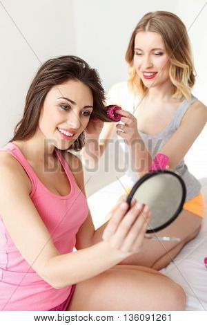 Carefree two girls making pajama party. Woman is twisting curlers on female hair and smiling. Her friend is looking at mirror with satisfaction. They are sitting on bed