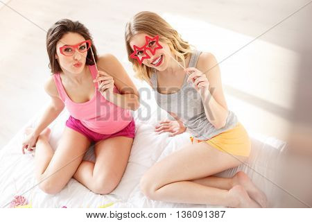 Joyful young women having fin at home. They are wearing paper eyeglasses and posing. Friends are sitting on bed and smiling