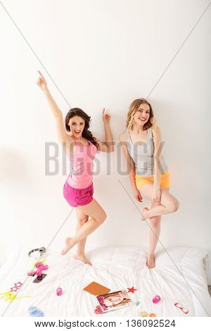 Happy two girls are making pajama party. They are standing on bed and posing. Friends are looking at camera and laughing